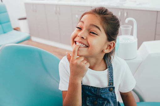 Little girl pointing at her teeth after her pediatric tooth extraction done at Surprise Oral & Implant Surgery in Surprise, AZ