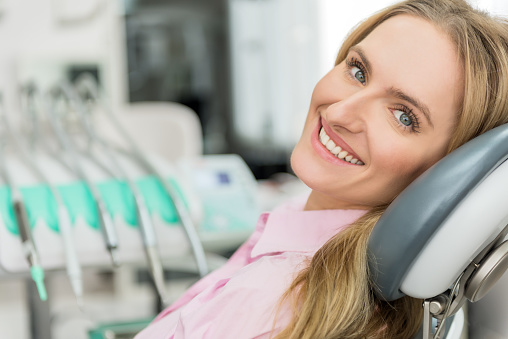 Blonde woman smiling in dental chair in Surprise Oral & Implant Surgery in Surprise, AZ