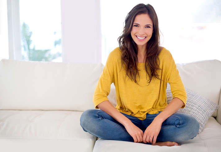A smiling woman sitting cross legged on a couch