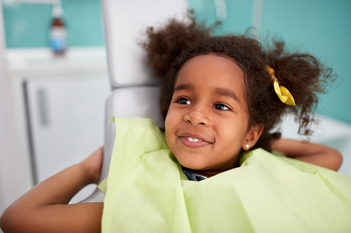 Adorable Black girl in the dental chair about to get pediatric oral surgery done at Surprise Oral & Implant Surgery in Surprise, AZ