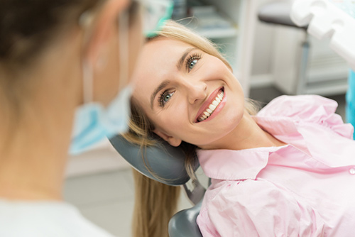 A smiling woman looking at dentist